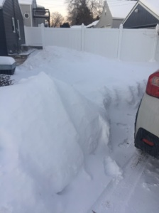 Part of my car next to a snow pile about 4 feet high
